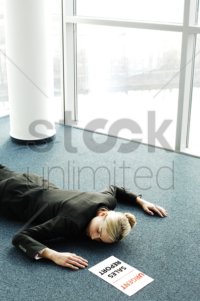 businesswoman fainted on the floor while rushing to submit an urgent sales report stock photo