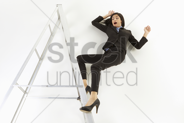 businesswoman falling off a ladder stock photo