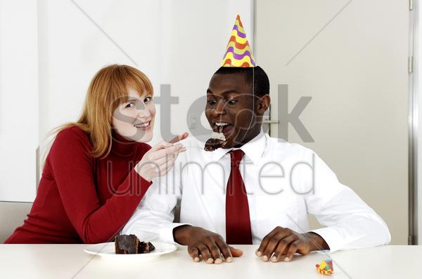 businesswoman feeding her colleague cake stock photo