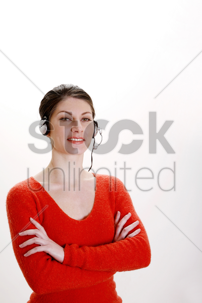 businesswoman folding her arms while talking on the headset stock photo