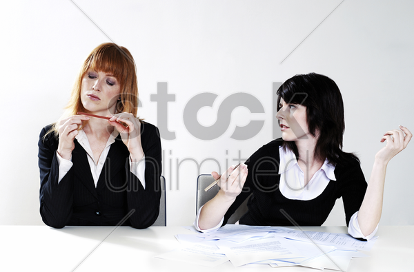 businesswoman getting frustrated with her colleague for not doing her work stock photo