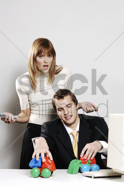 businesswoman getting irritated with her colleague's playful behaviour stock photo