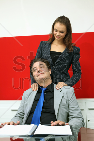 businesswoman giving businessman a shoulder massage stock photo