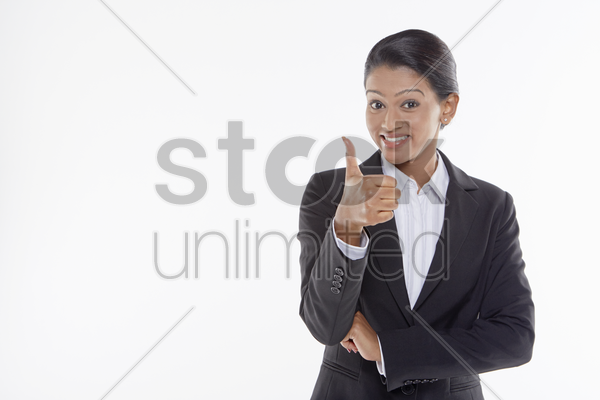 businesswoman giving thumbs up stock photo