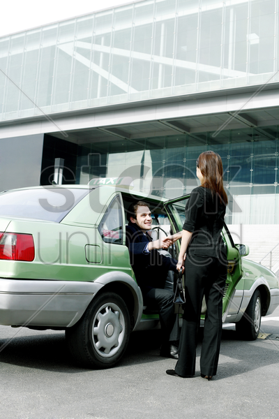 businesswoman greeting her client from the taxi stock photo