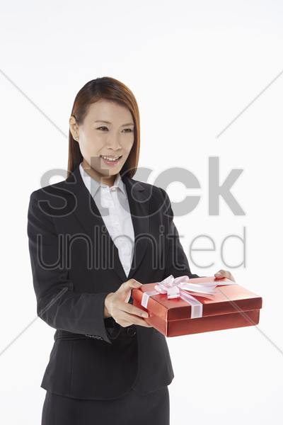 businesswoman handing out a gift box stock photo