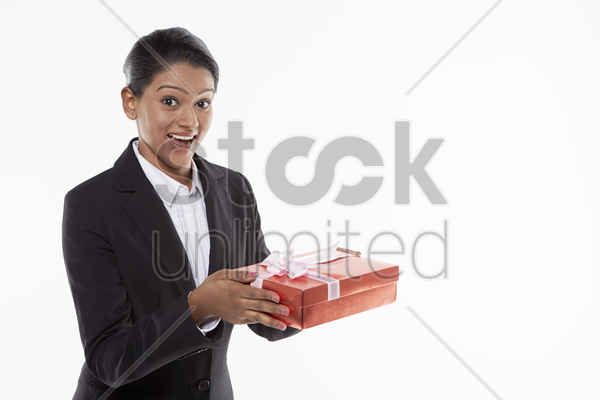 businesswoman handing out a red gift box stock photo