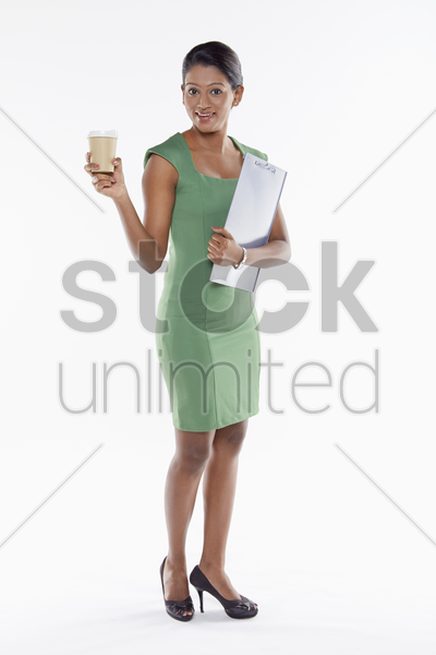 businesswoman having a drink while holding document stock photo