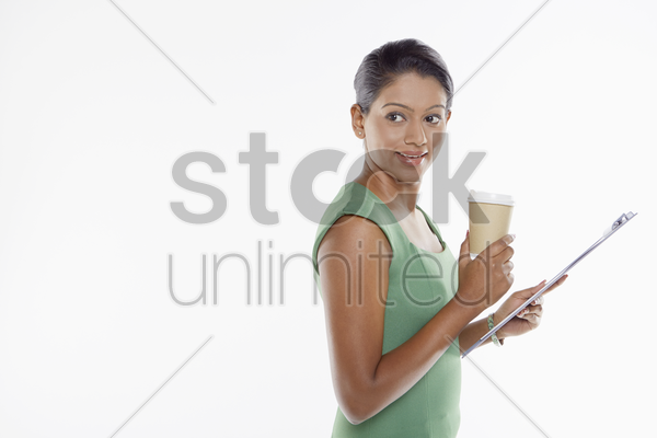 businesswoman having a drink while looking at document stock photo