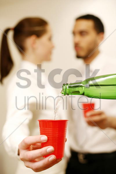 businesswoman having her drinks refilled while talking to her colleague stock photo