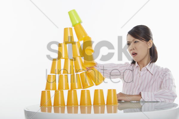 businesswoman hitting pyramid of disposable cups stock photo
