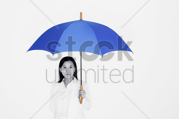 businesswoman holding a blue umbrella stock photo