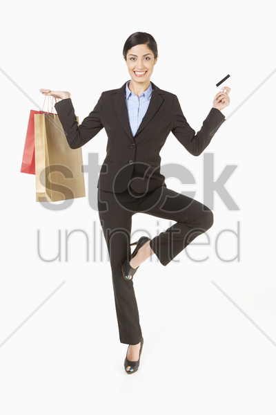 businesswoman holding a credit card and shopping bags, standing in a yoga position stock photo