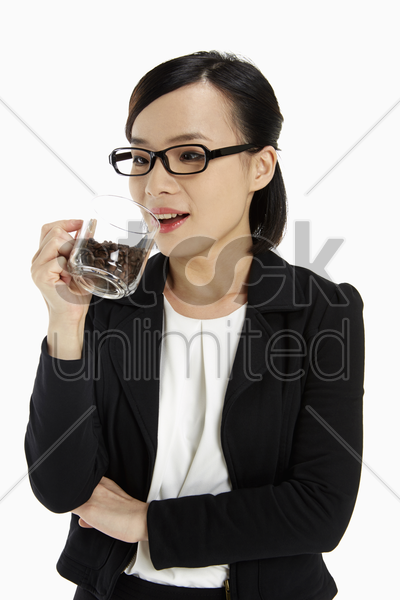 businesswoman holding a cup filled with coffee beans stock photo