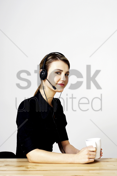 businesswoman holding a cup of coffee while answering calls stock photo