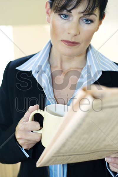 businesswoman holding a cup of coffee while reading newspaper stock photo