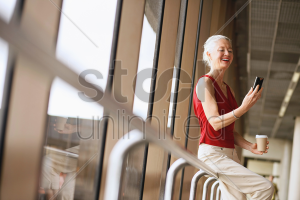 businesswoman holding a cup of coffee while reading text message in phone stock photo