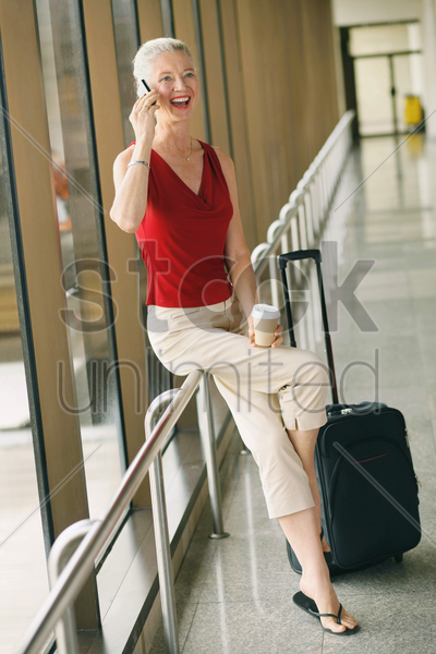 businesswoman holding a cup of coffee while talking on the phone stock photo