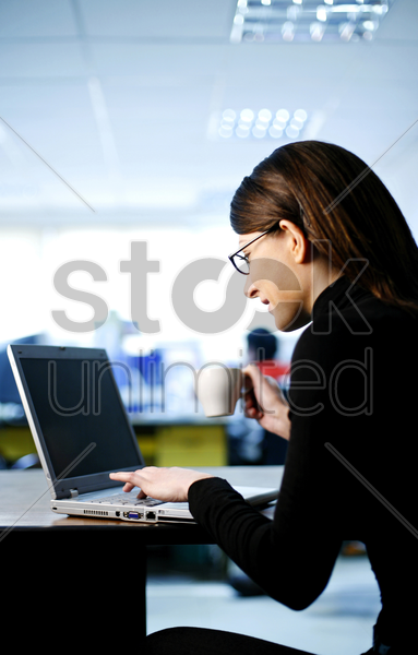 businesswoman holding a cup of coffee while using laptop stock photo
