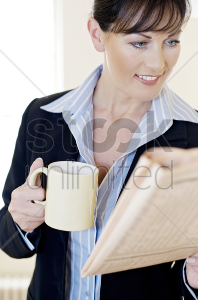 businesswoman holding a cup while reading newspaper stock photo