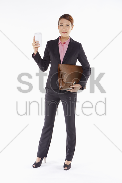 businesswoman holding a disposable cup and a briefcase stock photo