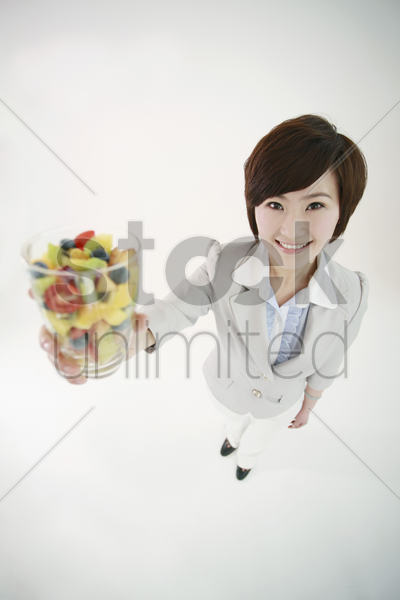 businesswoman holding a glass of mixed fruits stock photo