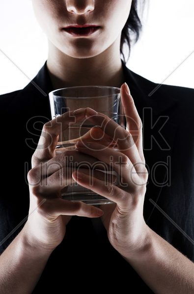 businesswoman holding a glass of water stock photo