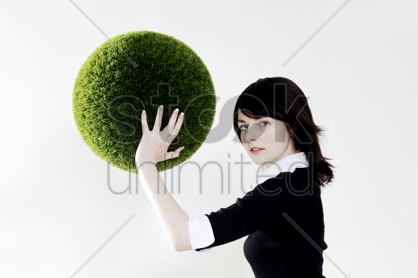 businesswoman holding a grass ball stock photo