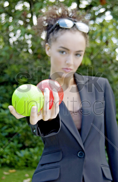 businesswoman holding a green and a red ball stock photo