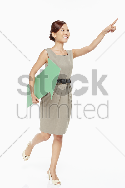 businesswoman holding a green arrow, facing left stock photo