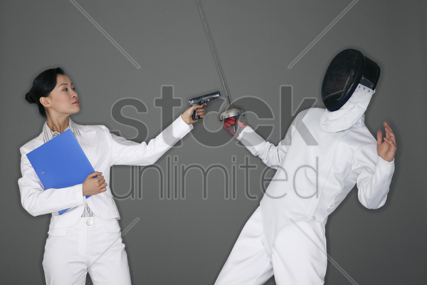 businesswoman holding a gun at a man stock photo