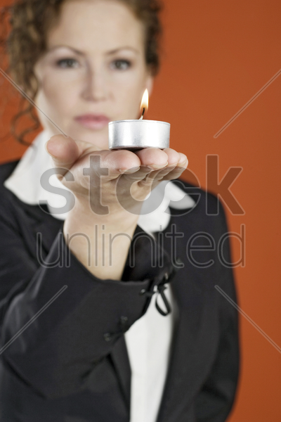 businesswoman holding a lit candle stock photo
