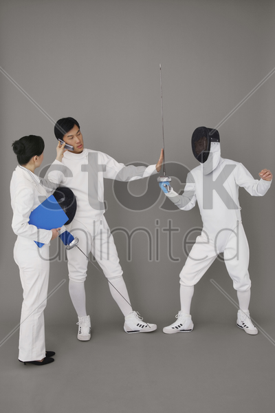 businesswoman holding a mobile phone for a man while he stops the fencing competition stock photo