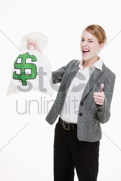 businesswoman holding a money bag and showing thumbs up stock photo