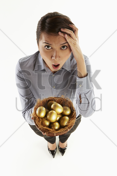 businesswoman holding a nest filled with golden eggs stock photo