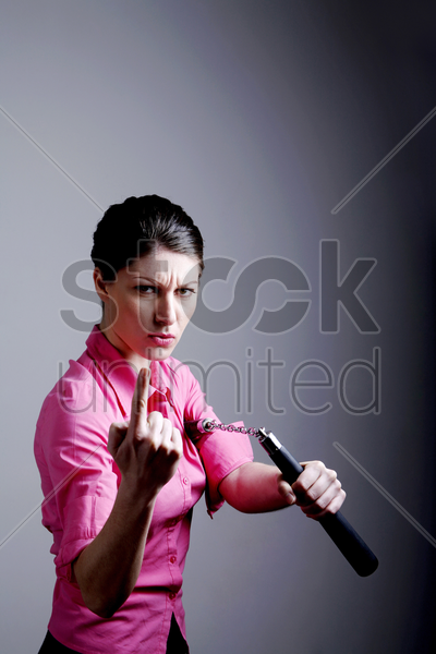 businesswoman holding a nunchaku inviting people for a challenge stock photo