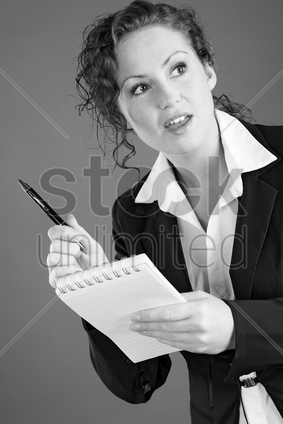 businesswoman holding a pen and a notepad stock photo