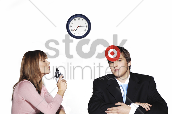 businesswoman holding a pistol targeting at her subordinate stock photo