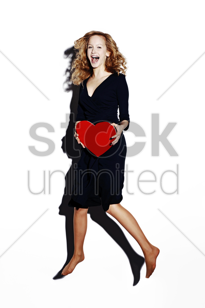 businesswoman holding a red heart stock photo