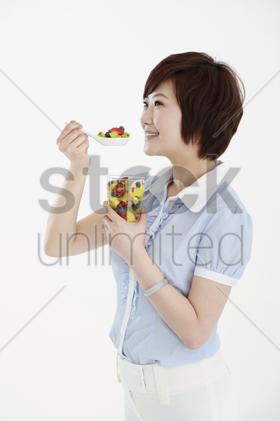 businesswoman holding a spoonful of mixed fruits stock photo