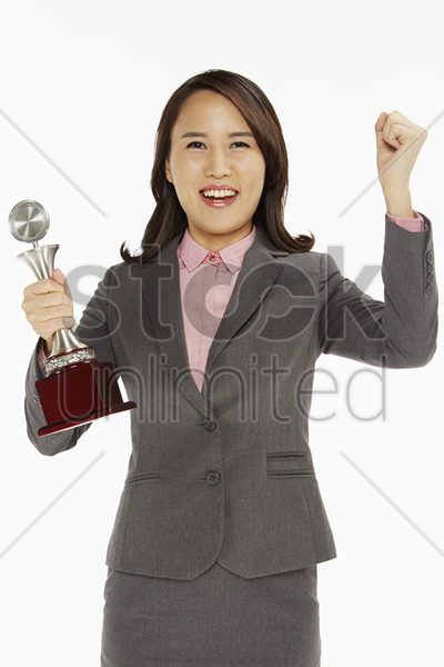 businesswoman holding a trophy and cheering stock photo