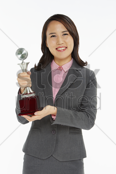 businesswoman holding a trophy stock photo