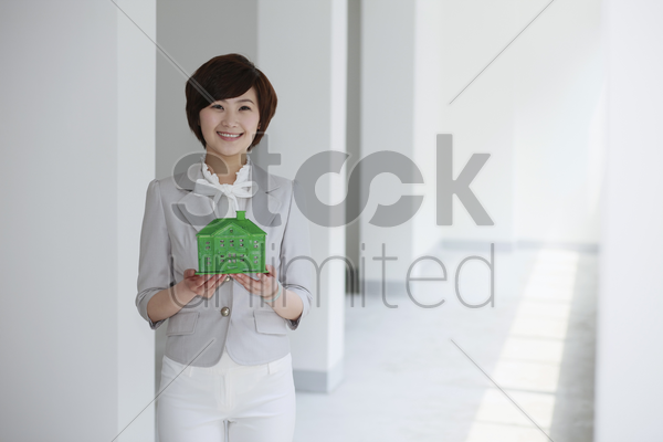businesswoman holding a wooden house model stock photo