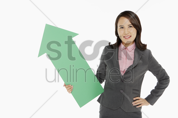 businesswoman holding an arrow, pointing upwards stock photo