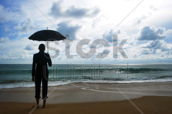 businesswoman holding an umbrella on the beach stock photo