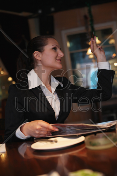 businesswoman holding credit card and gesturing to waiter stock photo