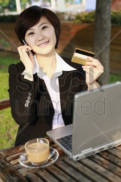 businesswoman holding credit card while talking on the phone stock photo