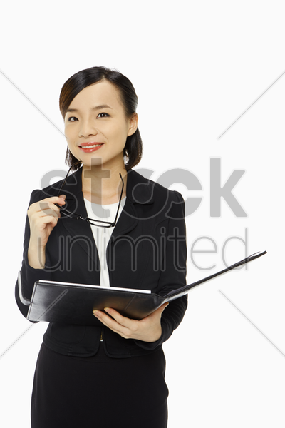 businesswoman holding her spectacles and smiling stock photo