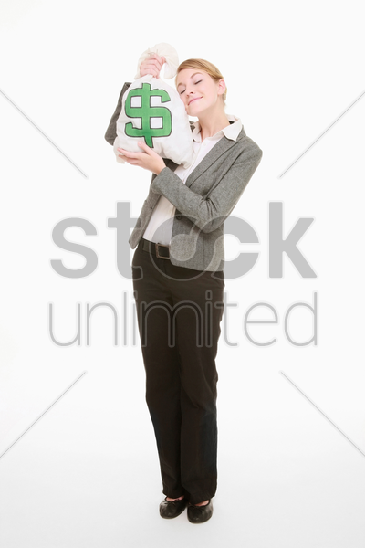 businesswoman holding money bag close to her face stock photo