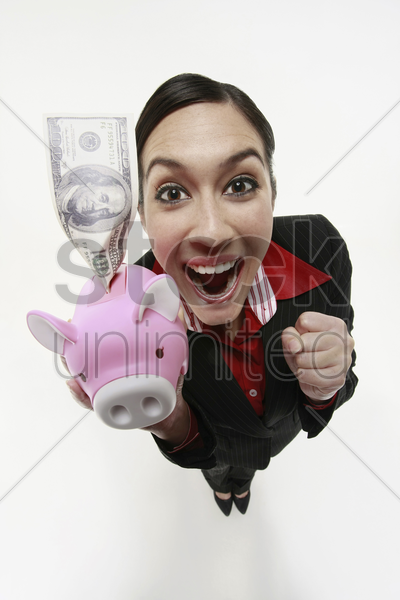 businesswoman holding piggy bank with money stock photo